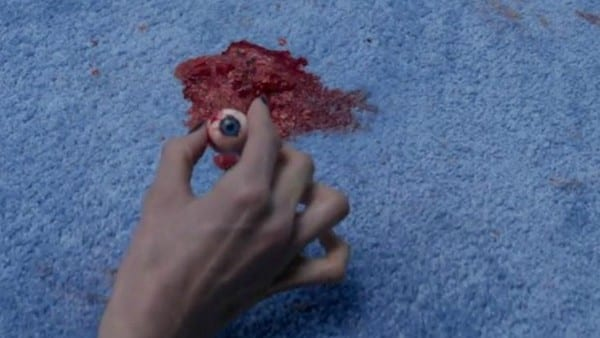 a hand picks up an eyeball sitting in a pool of blood on a carpet
