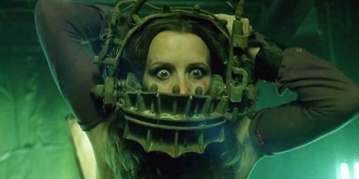 Close up of wide-eyed woman struggling with torturous device clamped around her head in Saw.