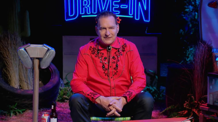 Joe Bob sitting in front of The Last Drive-In sign