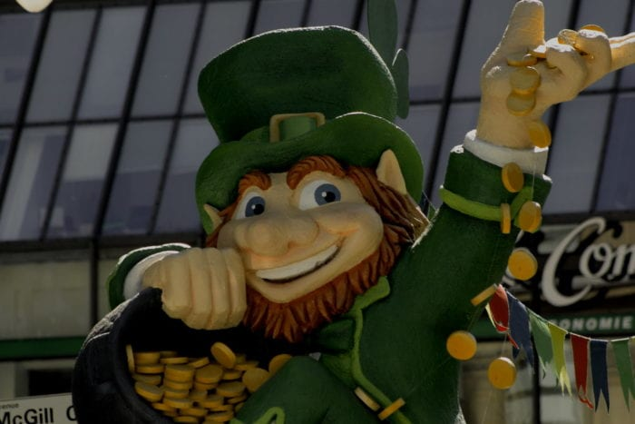 A smiling leprechaun waves as he holds his legendary pot of gold.a