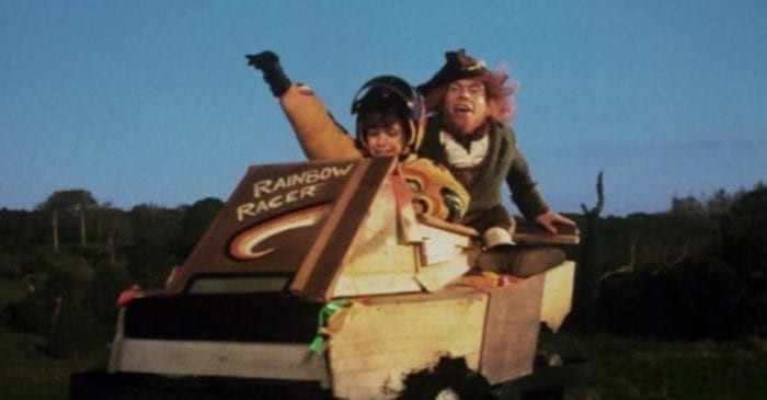 A smiling child puts her arm up as she steers a go cart while a green clad leprechaun sits behind her.