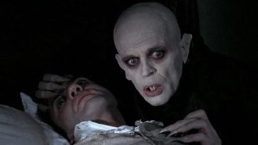Dracula holding Jonathan Harker and looking concerned