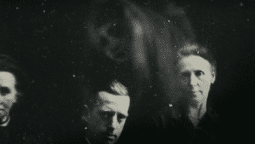 An old black and white photo of three stern looking people, with what looks like a ghostly apparition hovering above them.