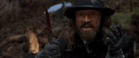 a wide-eyed man in a hat holds a knife covered in blood