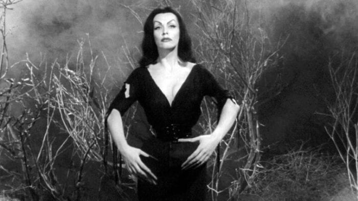 A curvy woman with long black hair, dressed in a form-fitting black dress stands in a fog.