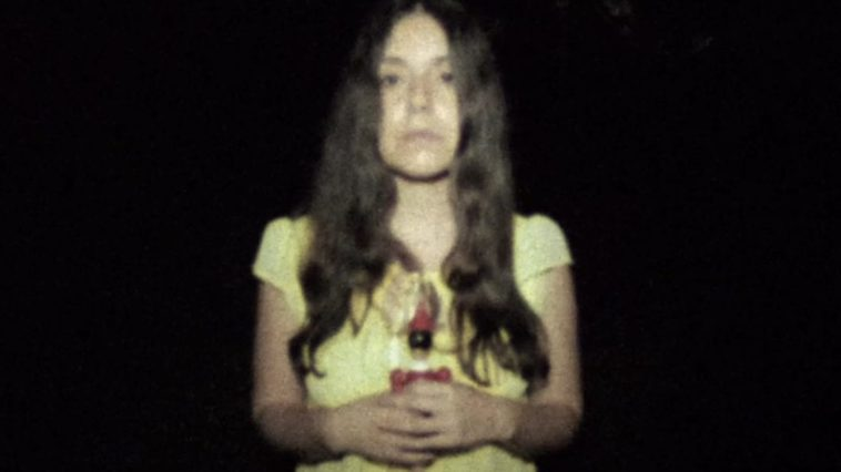 Altair stands in the camera light surrounded by darkness, holding a wooden doll