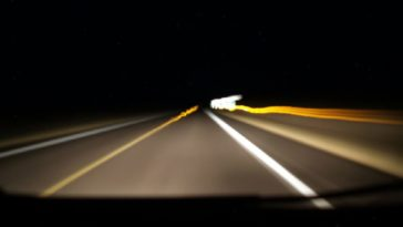 Blurred image of headlights shining on an extremely dark highway.