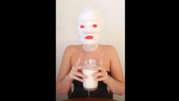 Harley Dee sits at a table with gauze wrapped around her head, lipstick pained on where her eyes and lips would be, raising a glass of milk with both hands