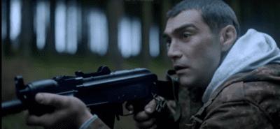 A scared man holds a gun