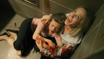 Screaming for help, Marcy holds an injured woman in the corner of a bathroom.