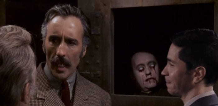 "Simon (Justin Long) smiles with glee as he looks at Professor Sir Alexander Saxton (Christopher Lee), with a blind corpse with bleeding eyes in the background, while inside the film, ""Horror Express"" (1972), from the TV show, ""Creepshow."""