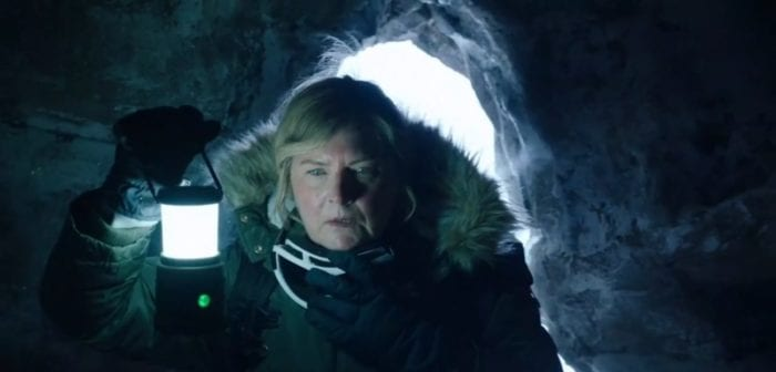 Dr. Trollenberg in a heavy winter jacket enters a cave with a lantern.