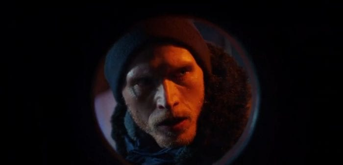 Carson looks through a porthole toward the camera