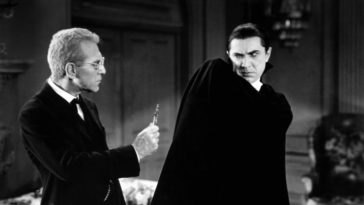 Dracula recoils from a cross presented by doctor Helsing