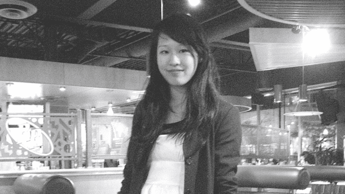 In this image, Elisa Lam is standing in a shop. She is smiling a little. The picture is in black and white.