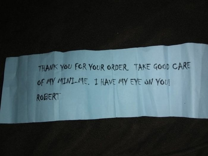 """A message in black print on a light blue strip of paper reads: """"Thank you for your order. Take good care of my mini me. I have my eye on you."""
