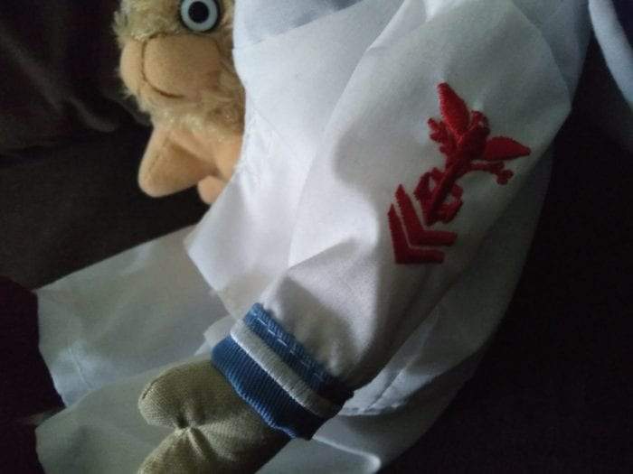 A close up of red embroidered symbol on arm of doll's white jacket.