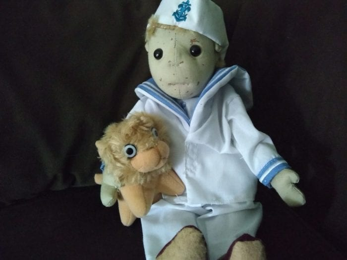 A plush male doll dressed in a sailor suit holds a plush lion.