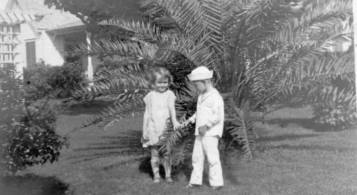 Two children---a girl and a boy dressed in a sailor suit walk outdoors.