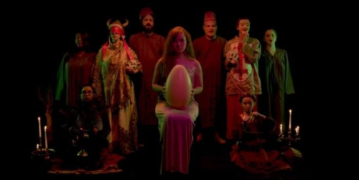 Karen sitting in a dress holding a giant egg in her lap, is surrounded by many people all staring into the camera