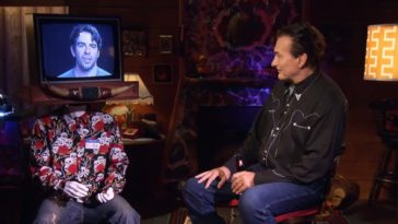 Joe Bob sitting and talking to Eli Roth on a monitor