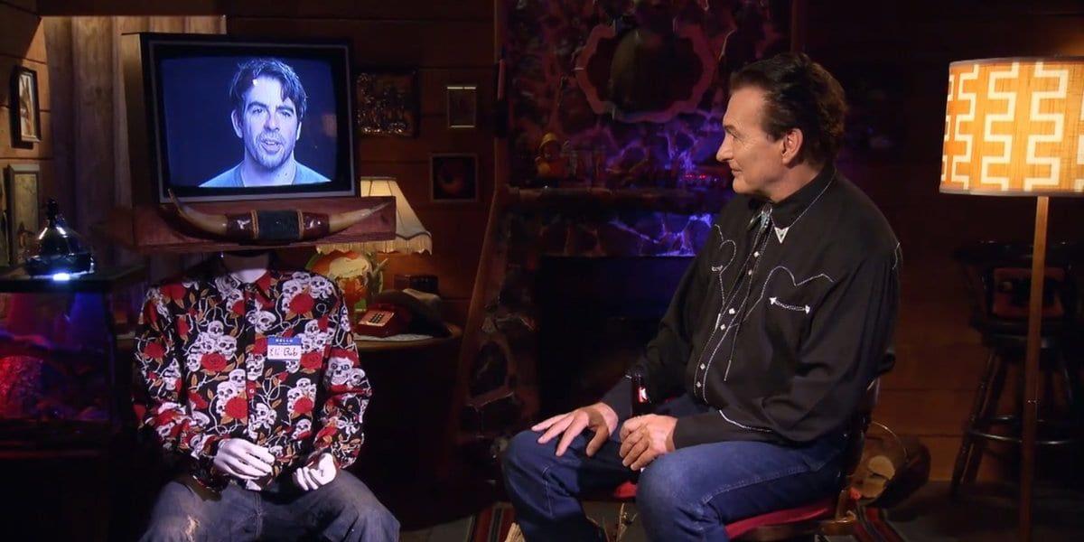 Joe Bob sitting and talking to Eli Roth on a monitor