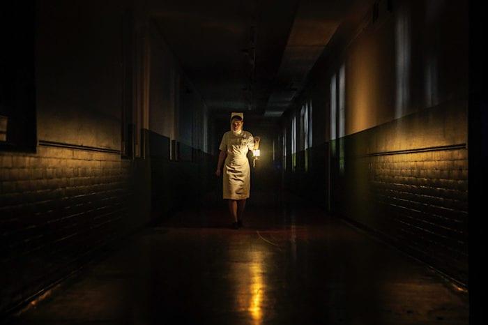 Nurse Val walks alone down a dark hospital hall at night