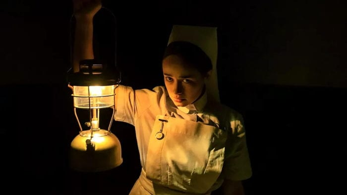 Nurse Val peers into the dark hallway carrying a light lamp