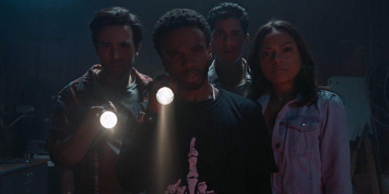 Brian, Alex, Louis, and Jess look toward the camera shining flashlights