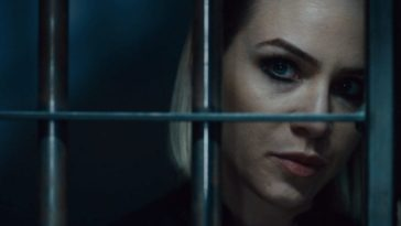 A blonde woman looks through the bars of a jail cell in Vicious Fun