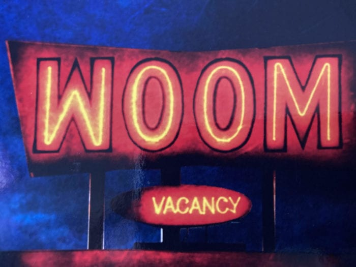 Cover art for Woom shows the title done as a motel sign. A sign saying vacancy sits below it.