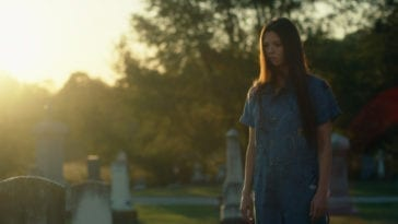 A woman in a blue dress in a graveyard at sunset in She Watches from the Woods