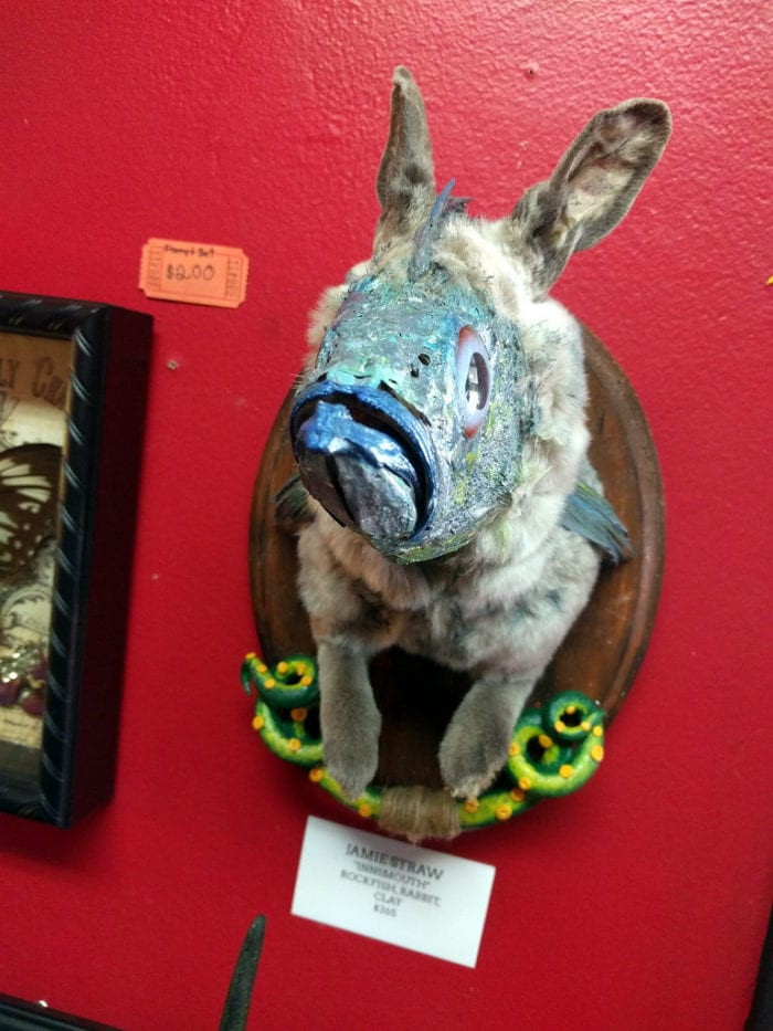 A rabbit's head with a fish's face mounted to a red wall.
