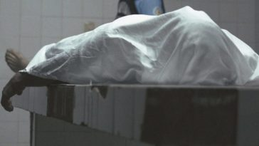 A body lies on a morgue table under a sheet, arm and bare feet visible.