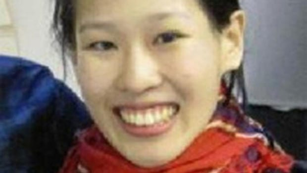 In this image, Elisa Lam was wearing a red scarf and smiling.