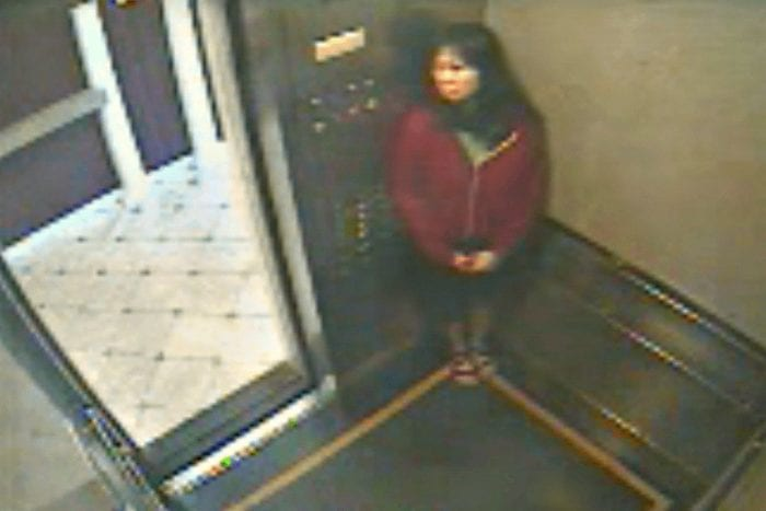 In this image Elisa Lam is seen hiding in the elevator wearing a red sweater and a black skirt.