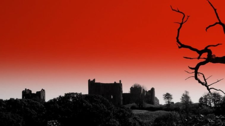 Red sky background behind a gothic building.