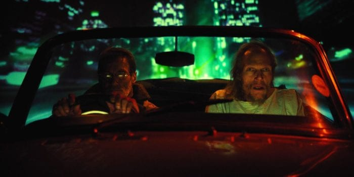 Barry and another man in a car with rear-projection behind them