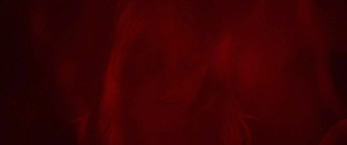 Close-up of young woman cast in red light looking downward.