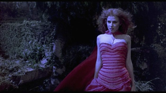 A red-haired woman in a bright red dress, revealing dress walks at night, looking as if in a daze..