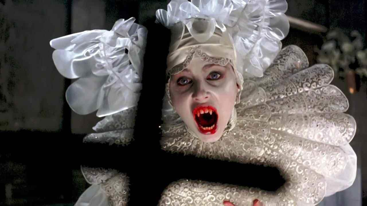 A female vampire snarls, baring her fangs, recoiling from a crucifix, seen in silhouette in the foreground