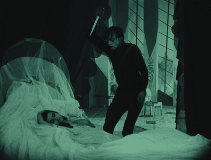 Cesare stands holding a knife over a sleeping woman
