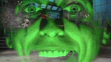 "Alice Cooper's face, lit up green, is superimposed over a dungeon, in the TV show, ""The Muppet Show."""