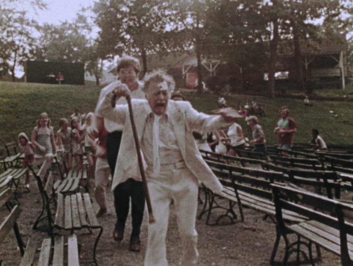 An older man in a white suit with a cane appears to run from a younger man and a bunch of children amid park benches.