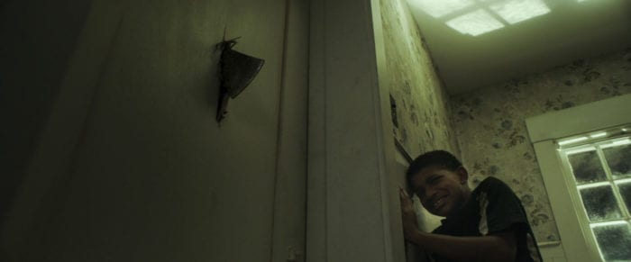 A young boy cowers in a room terrified as an axe blade plunges through the door.