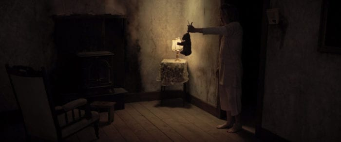 A child standing in a shadowy bedroom holds a rabbit by its ears