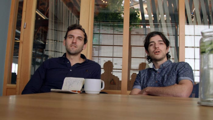 Two men sit at a table and look across at the camera/viewer. A cup of coffee and notebook sit in front of one man on the table.