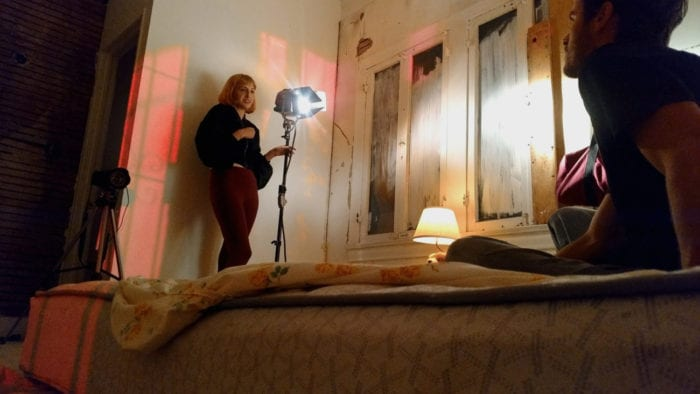 Horvat stands against a wall in a bedroom and adjusts lighting for a scene while a man sits on the bed,.