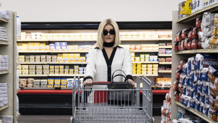 A woman with dark sunglasses pushes a shopping cart down a supermarket aisle