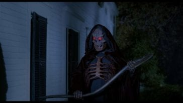 Grim Reaper standing outside a house with scythe in hand